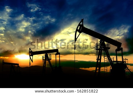 Oil pumps jack.Oil industry equipment working on sunset background - stock photo