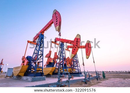 oil pumps working at oilfiled at dusk - stock photo