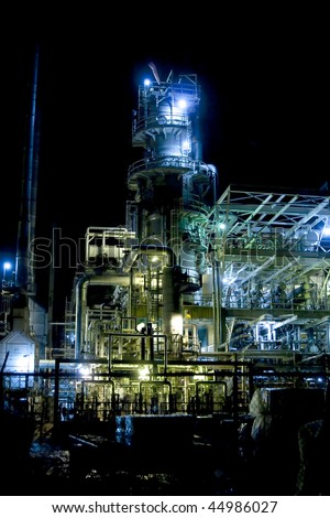 oil refinery at night with mixed color lighting - stock photo