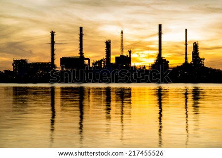Oil refinery factory in silhouette and sunrise sky - stock photo