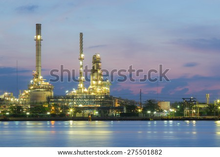Oil refinery factory river front, twilight
