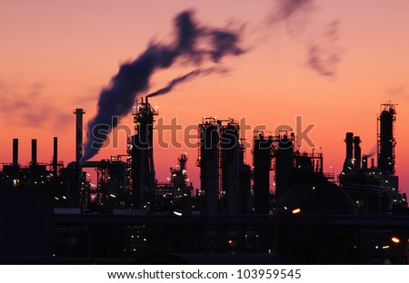 Oil refinery factory silhouette over sunset