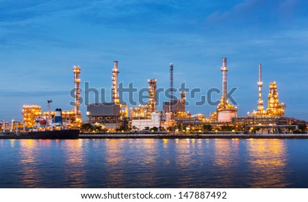 Oil refinery plant near river in twilight - stock photo