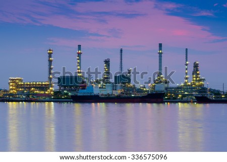 Oil refinery reflected along with river during twilight