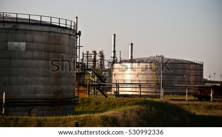Oil refinery tanks and pipes under the afternoon sun