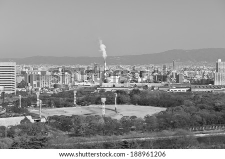 oil refinery with smoke stacks against. black and white photo.