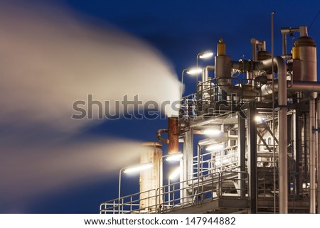 Oil refinery with water vapor, petrochemical industry night scene - stock photo