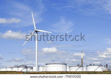 oil refinery with wind turbine for clean energy - stock photo