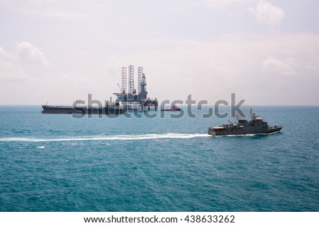Oil rig and oil tanker ship with patrol vessel sailing pass in the gulf - stock photo