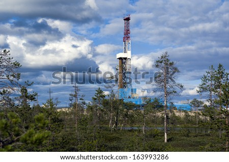 Oil rig and small forest on foreground - stock photo