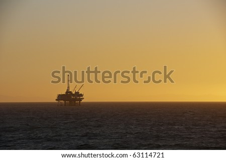 Oil Rig at sunset in Huntington Beach. - stock photo