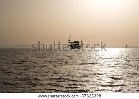 Oil rig in the Red Sea under brown sky.