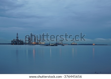Oil rig with blue hour and formation of cloudscape. Bad weather, oil and gas environment