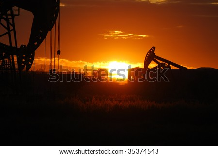 oil rigs silhouette over orange sky