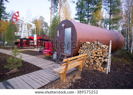Oil rocking and residential trailer-a barrel with a stock of firewood in the forest. - stock photo