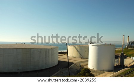 Oil storage tanks at a refinery on the sea - stock photo