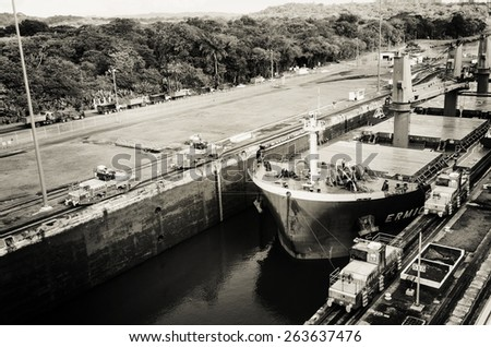 Oil tanker, assisted by tugboats, are preparing to transit the Panama Canal to the west towards the Pacific. - stock photo