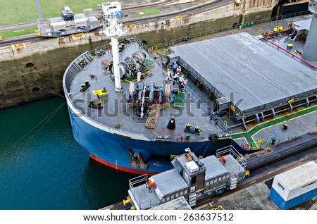 Oil tanker, assisted by tugboats in Panama Canal  - stock photo