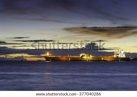 Oil Tanker loading oil in the sea at twilight - stock photo