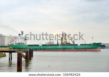 oil tanker sailing out of the harbor of rotterdam - stock photo