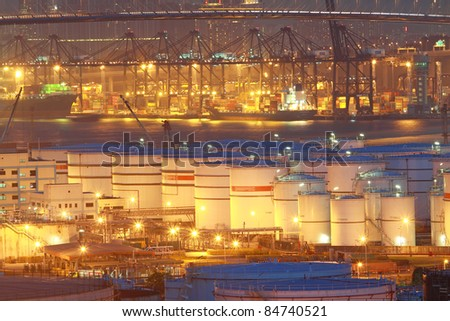 Oil tanks at night in container terminal - stock photo