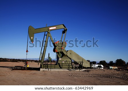 Oil well in the desert with blue sky - stock photo