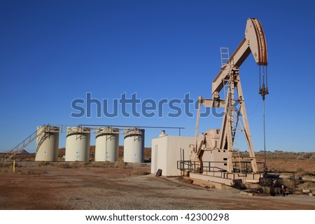 Oil well with Storage Tanks in the tackground - stock photo