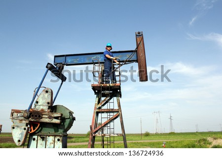 oil worker and pump jack industry scene - stock photo