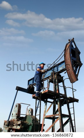 oil worker climbs up to the pump jack - stock photo