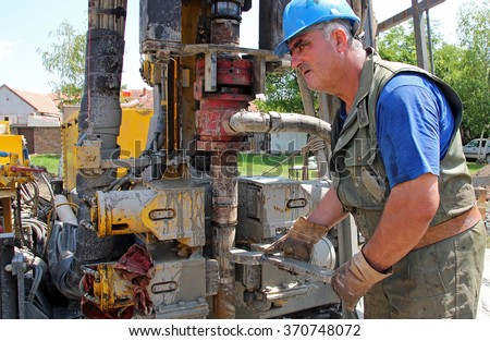 Oil Worker Drilling For Oil on Rig. Portrait of an oil worker with tool in his hands. Worker operating machinery on oil rig. Oil and Gas Industry. Selective focus. - stock photo