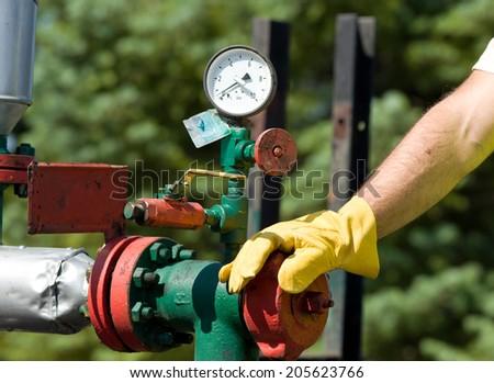 Oil worker examining barometer on oil plant - stock photo