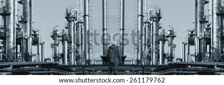 oil worker in front of giant refinery, mirror image concept - stock photo