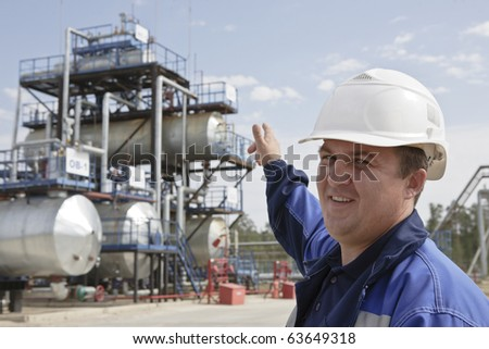 Oil worker in industrial oil and fuel plant - stock photo