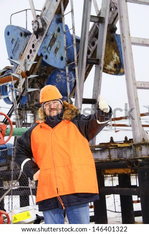 Oil worker in orange uniform and helmet on of background the pump jack. - stock photo