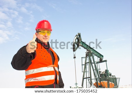 Oil worker in orange uniform and helmet on of background the pump jack.  , best focus on the helmet, vest and glasses, pump soft focus - stock photo