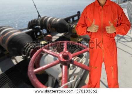 Oil worker in orange uniform and helmet on of rig background