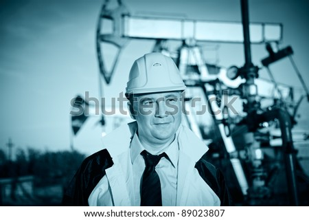 Oil worker in uniform and helmet on of background the pump jack and sky. Toned. - stock photo
