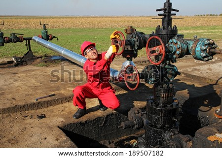 Oil Worker. Oil and gas Industry.  Worker in action at pump jack oil well.  - stock photo