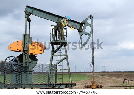 oil worker standing at pump jack
