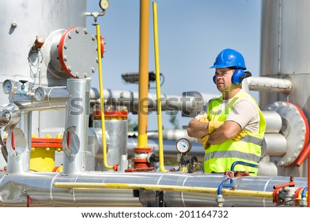 Oil worker supervising gas pressure in pipelines on plant - stock photo