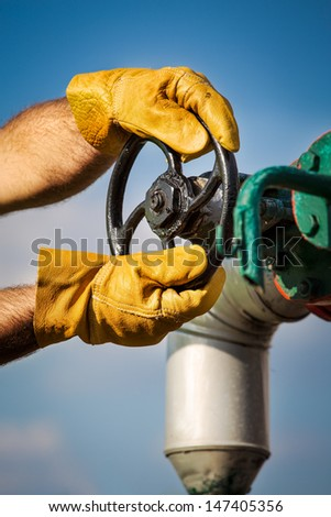 oil worker turning valve - stock photo
