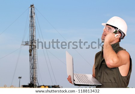 oil worker with laptop and rig - stock photo