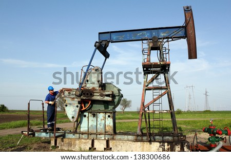 oil worker working on pump jack - stock photo