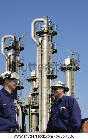oil workers and large chemical refinery, fuel-towers and pipelines - stock photo