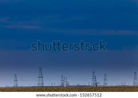 Oilfield with oil pumps and oil rigs profiled on blue sky - stock photo
