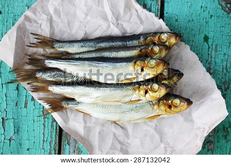 Oily fish is smoked on paper - stock photo