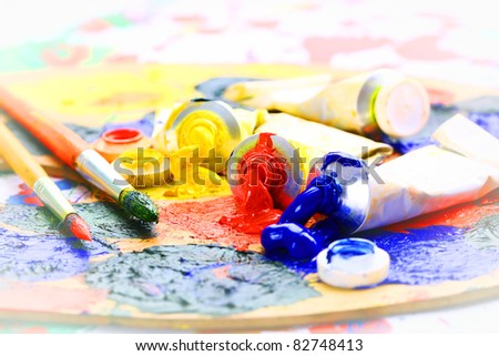 Oily paint brush to the palette on the colored background - stock photo