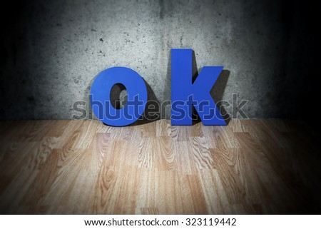 OK blue letters against an old cement wall - stock photo