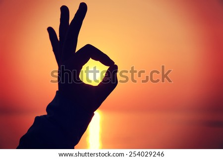 ok sign making of hands against bright sea sunset and sunny golden way at water - stock photo