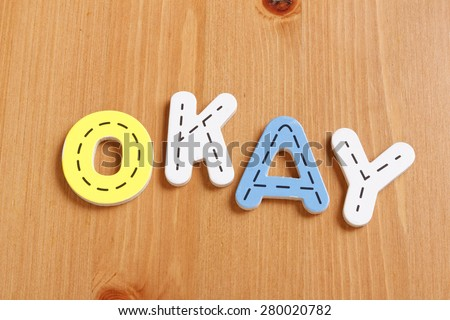 OKAY, spell by woody puzzle letters with woody background - stock photo
